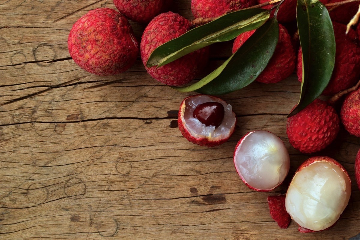 Lychees laying on a wooden table.