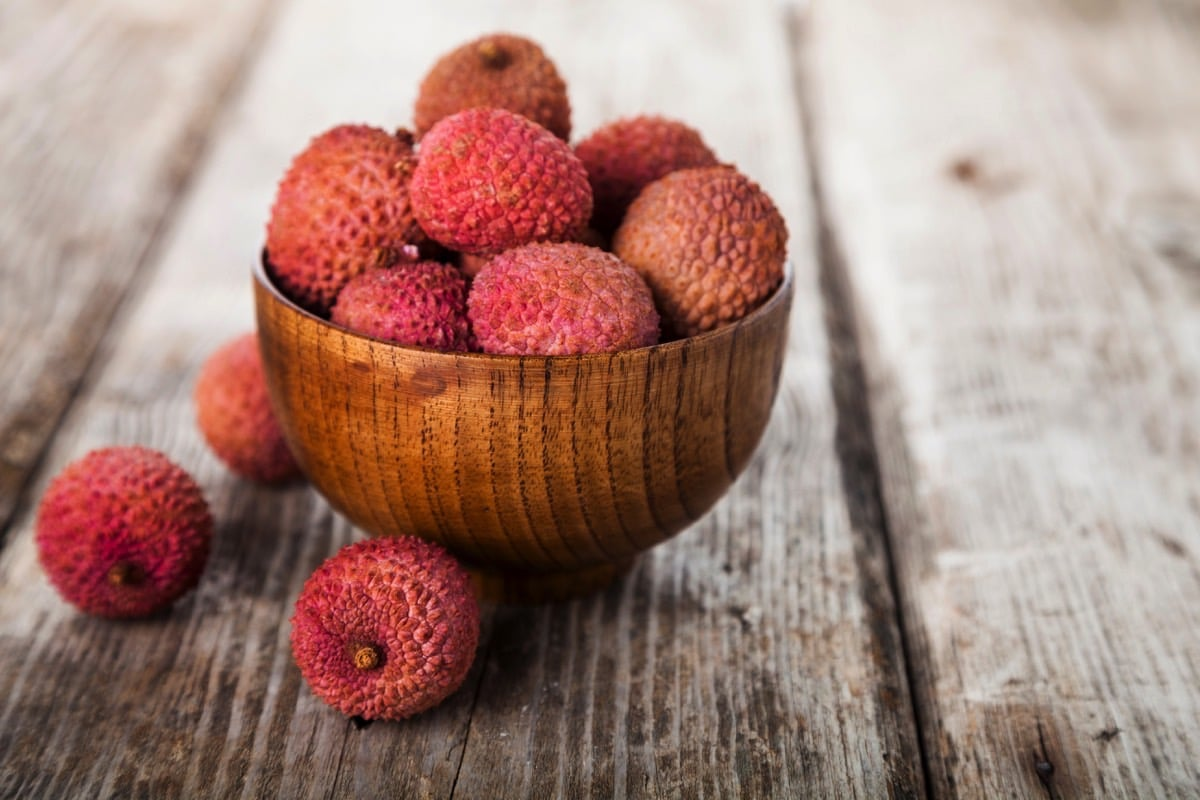 A wooden bowl filled with pink unpeeled lychees on a wooden background.