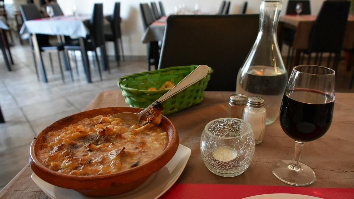 Cassoulet ready to eat with a red wine glass (Photo Credit: Castelnaudary.Le cassoulet. by Flickr User asipos49, original image has been adapted)