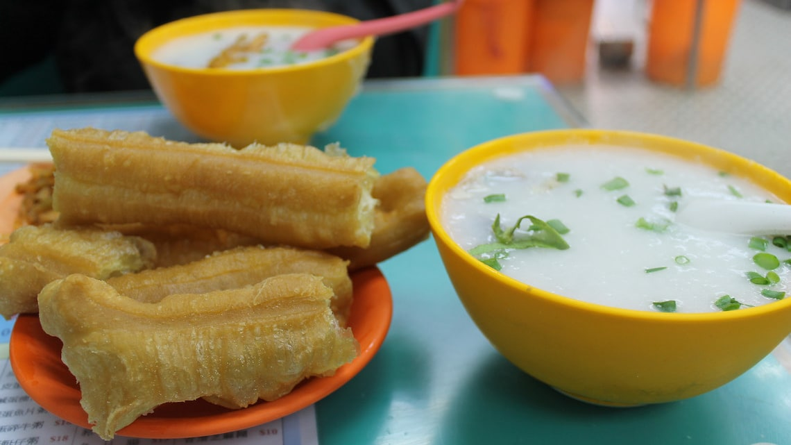 Congee topped with green onions and served with fried bread sticks.