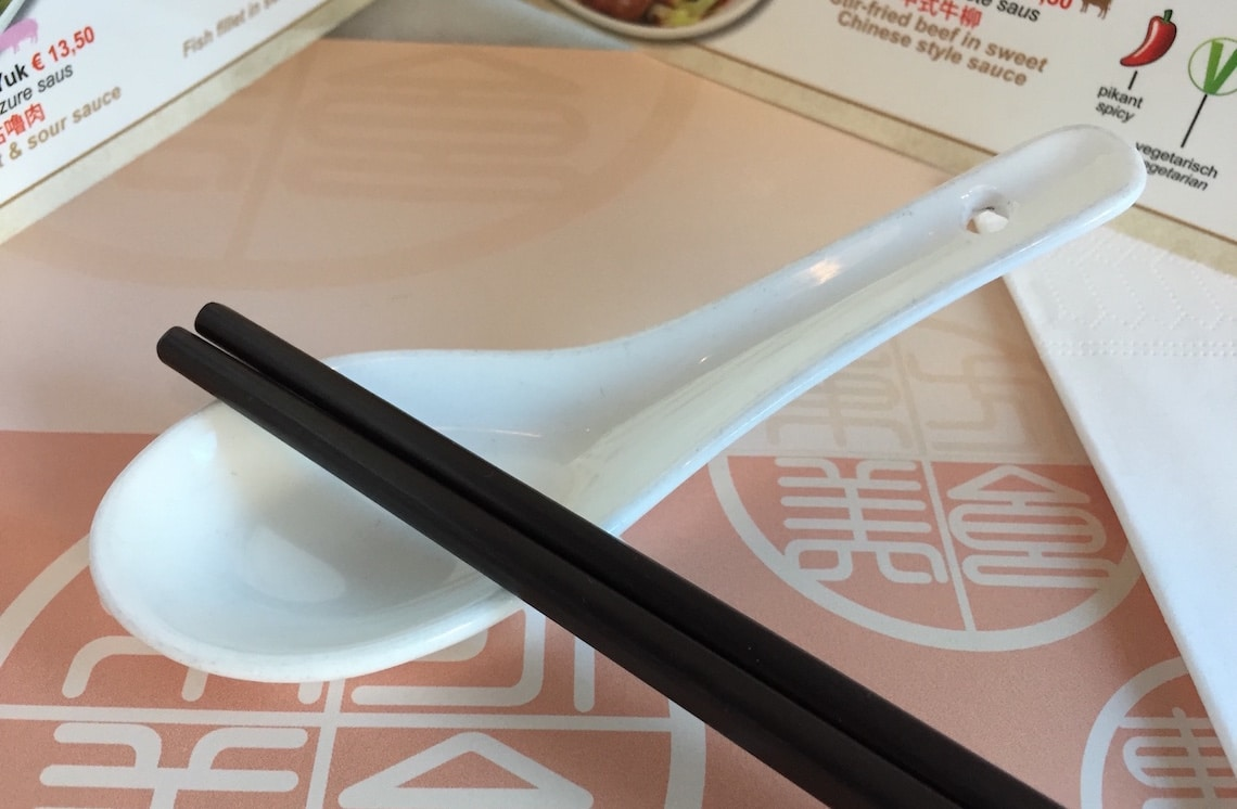 A Chinese spoon with a pair of chopsticks.