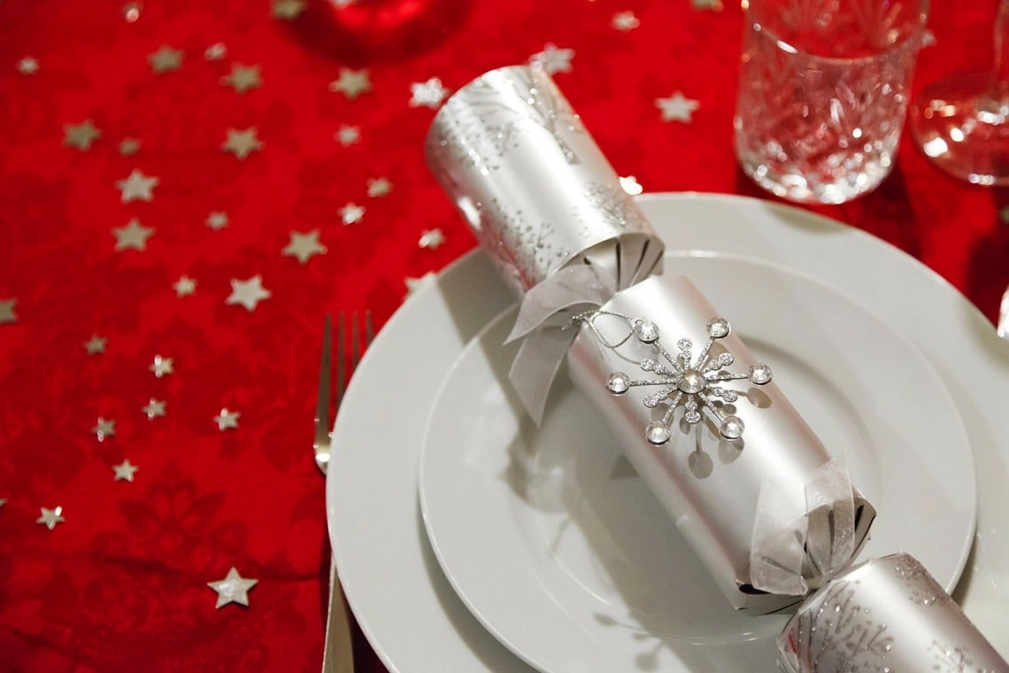 silver-Christmas-cracker-on-white-plates-on-red-tablecloth