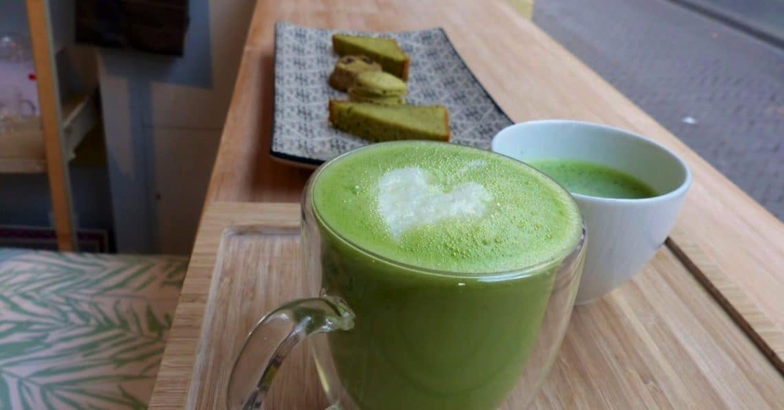 Mug full of matcha latte with matcha cake in the background