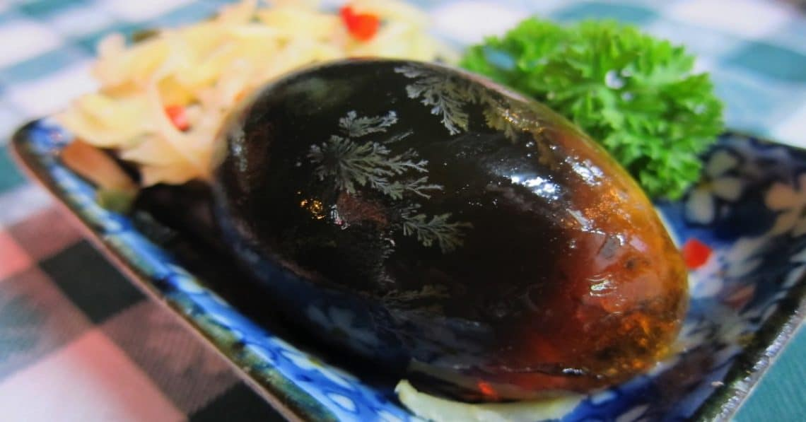 A dark brown century egg on a plate with parsley