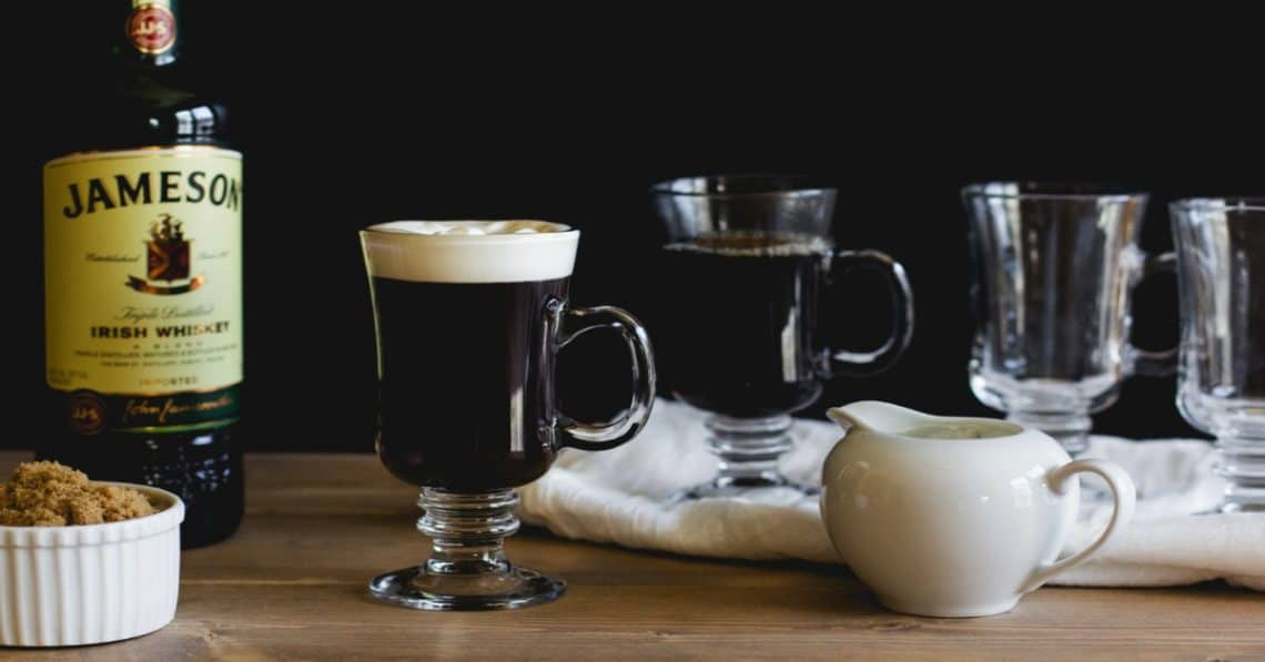 Irish Coffee in a glass with brown sugar and a bottle of Irish whiskey behind it