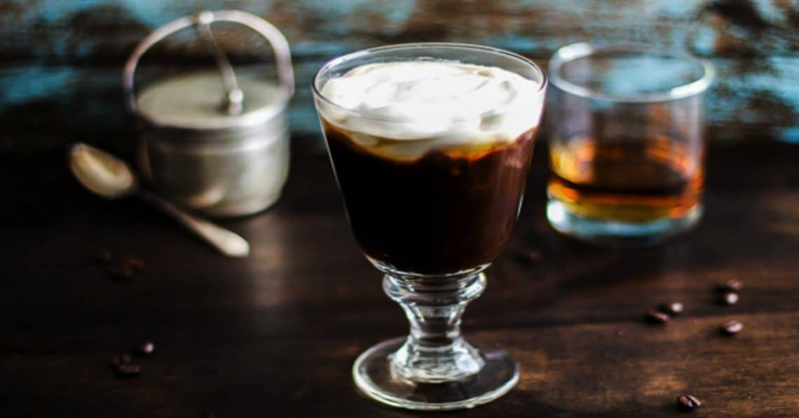 Irish coffee in a glass with a tumbler of whiskey and a pot of cream behind it