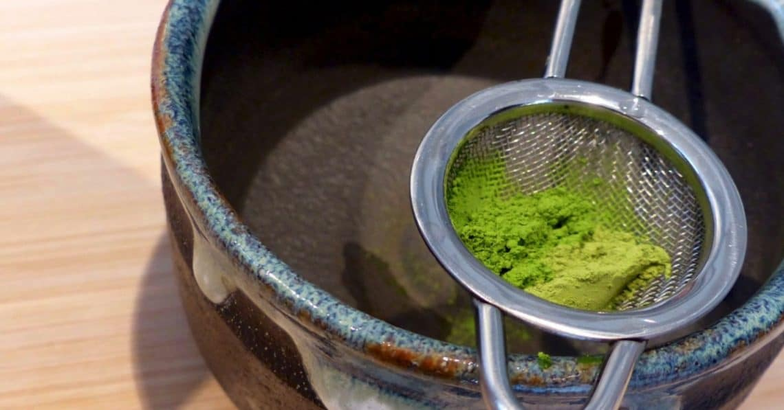 Matcha powder in a strainer above a mug