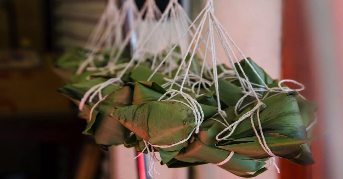 Zongzi (sticky rice dumplings) wrapped in leaves and hanging from string at the market