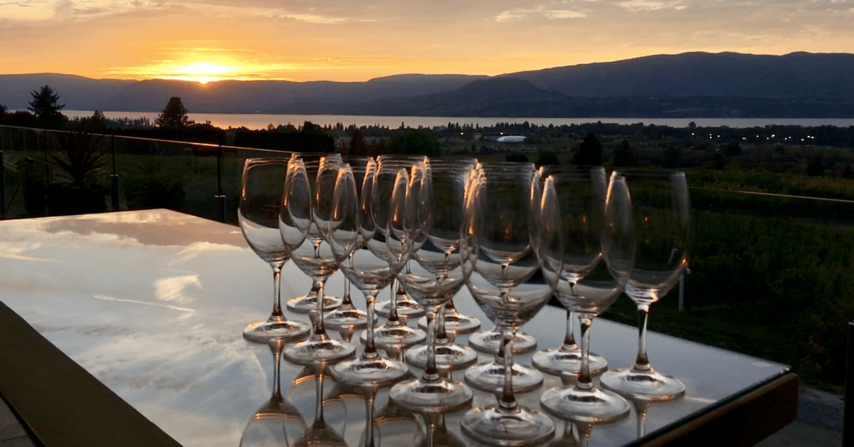 Wine glasses on a table while the sun sets in Okanagan.